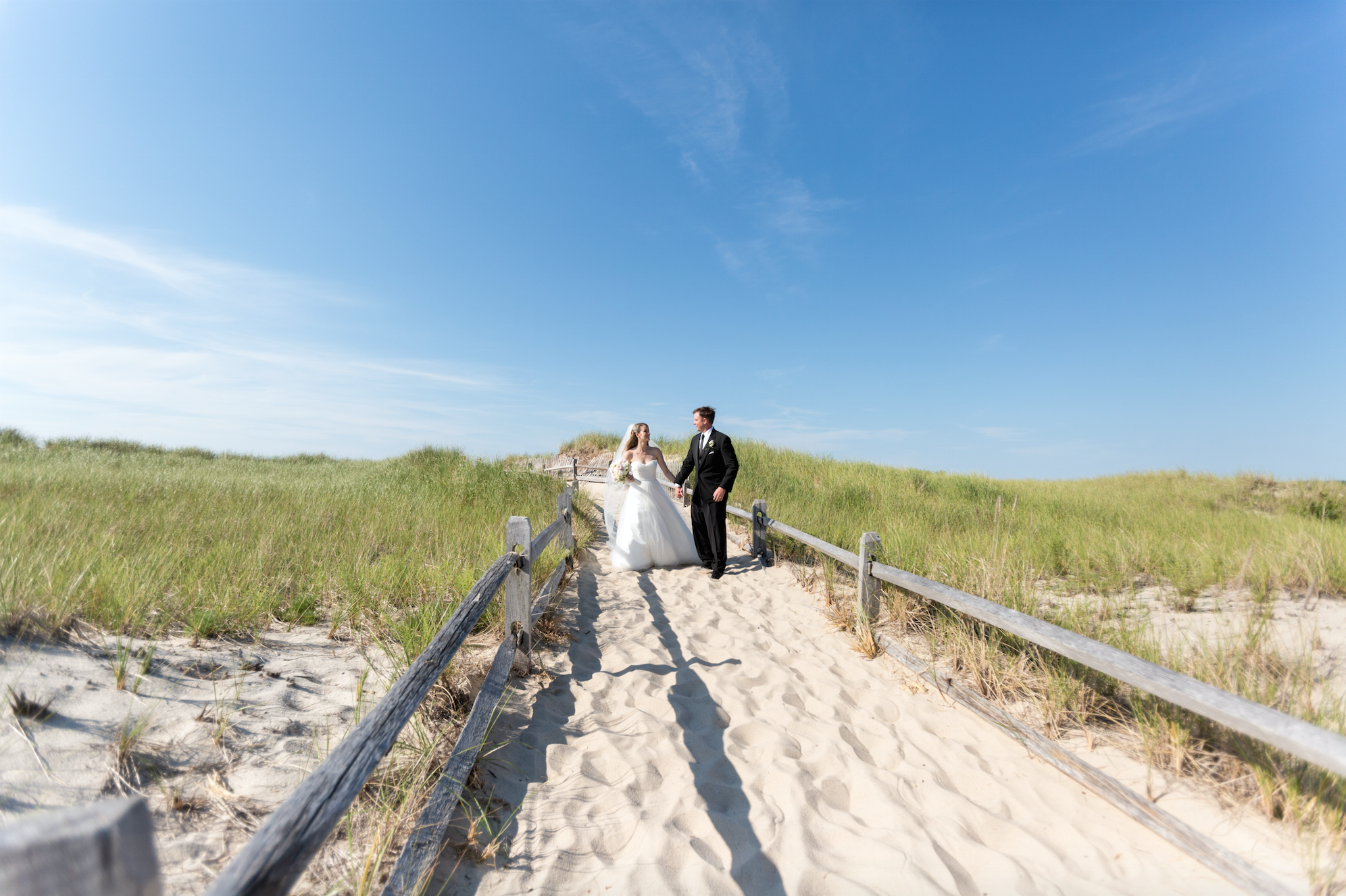 Bride and groom on beach path